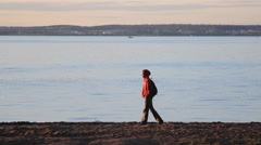 Man walking on the beach along the lake at sunset Stock Footage