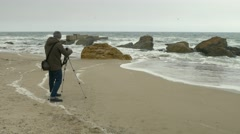 Photographer adjusts camera on tripod on sand beach near rocks and stormy sea. - stock footage