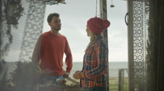 4K Young couple chatting at beach house, man gives woman a shell Stock Footage