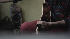 The guy playing the guitar and writing songs at home Stock Footage