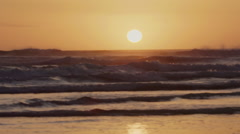 Tracking on ocean surf  at sunset on ninety mile beach, northland, new zealand Stock Footage