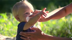 Mom wiped her daughter's mouth after feeding on a green meadow on a sunny day Stock Footage