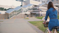 Back view of a brunette girl with long hair riding a bike in the city Stock Footage