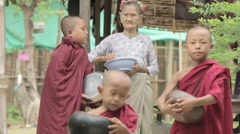 BAGAN, MYANMAR, July 4, 2016: Old Burmese woman giving alms to novice Buddhist m Stock Footage