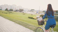Back view of a girl riding a bike with flowers and French bread in a basket Stock Footage