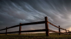 Fence in the field under stormy cloud sky. Stock Footage