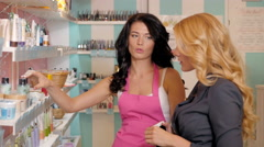 Pharmacist chemist woman helps to choose medicine for young to female buyer in Stock Footage