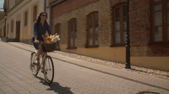 Beautiful girl walking down the street with a bike with flowers in a basket Stock Footage