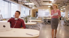 4K Businesswoman handing out papers to colleagues in modern creative office Stock Footage