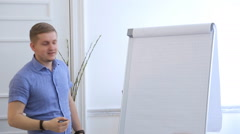 Blond man in blue shirt draws schemes on flipchart with white paper Stock Footage