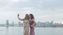 Two Attractive young women in party dresses on high hill get a selfie by - stock footage