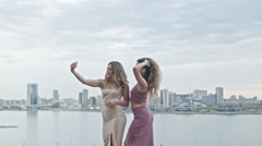Two Attractive young women in party dresses on high hill having fun get a selfie - stock footage