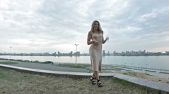 Attractive young woman fashion model in party dress posing outdoor in front of Stock Footage