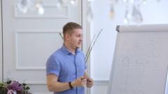 Blond man in blue shirt holds seminar in art workshop - stock footage