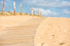 Wooden footpath through dunes at the ocean beach - stock photo
