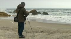 Photographer adjusts camera on tripod on sand beach near rocks and stormy sea. Stock Footage