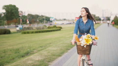 Side view of a girl cycling with flowers in a basket and exploring the city Stock Footage