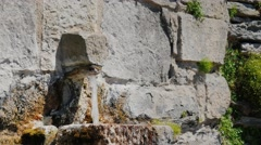 The water flows from the tap in the old stone wall. City Rupit Catalonia - stock footage