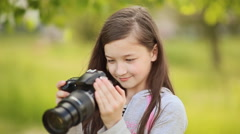 Small girl takes pictures on camera - stock footage