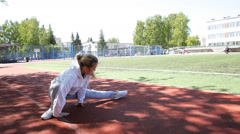 Young beauty girl do exercises at the stadium Stock Footage
