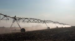 Center pivot irrigation system with drop sprinklers in field - stock footage