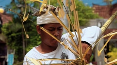 Balinese man decorating a penjor with palm leaf on Galungan Day Stock Footage
