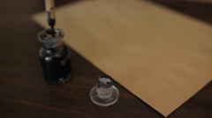 Female hand dipping a pen into an ink pot to write a letter Stock Footage