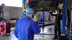 Garage owner talking with customer on phone and mechanic repairing car Arkistovideo