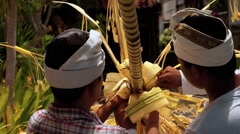 Two balinese men decorating a penjor with palm leaf on Galungan Day - stock footage