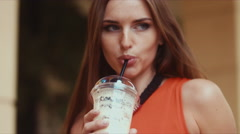 Urban portrait of young attractive Caucasian female drinking milkshake - stock footage