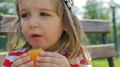 Sunny girl with apricot happily eating fruit Stock Footage