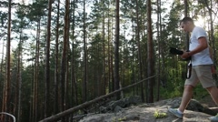 Male photographer is taking photographs in a forest at summer time. Stock Footage