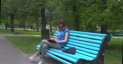 Girl with a laptop on a bench in the park Stock Footage