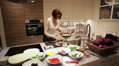 Woman Puts in Pizza Toppings in Kitchen Stock Footage