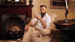 An aristocrat with a dog by the fireplace drinking whiskey. Stock Footage