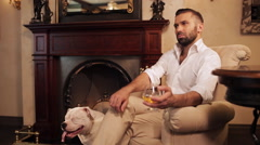 The man in the armchair by the fireplace drinking whiskey and petting his dog. Stock Footage