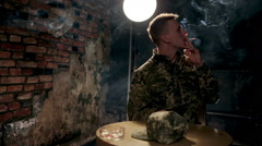 Young soldier nervously smoking in empty room Stock Footage