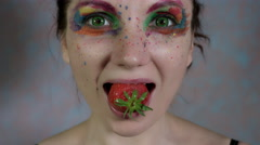 4k Shot of a Woman with Multicoloured Make-up with Strawberry in mouth Stock Footage