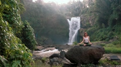 Woman doing yoga (Kapalbhati) in front of Tegenungan Waterfall, Ubud Stock Footage