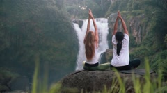 Two women practicing yoga lotus pose in front of Tegenungan Waterfall, Ubud Stock Footage