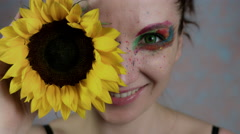 4k Shot of a Woman with Multicoloured Make-up With Sunflower (focus on flower) Stock Footage