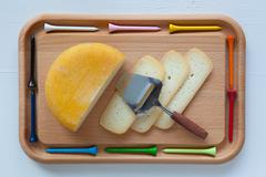 Block of tasty cheese on cutting board with a knife and golf tees Stock Photos