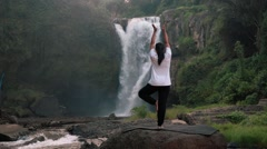Woman doing yoga (Tree Pose) in front of Tegenungan Waterfall, Ubud Stock Footage