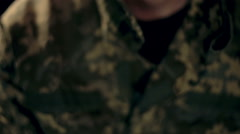 A soldier in military uniform on a black background has depressed look Stock Footage
