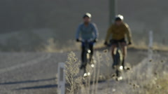 Couple of cyclists on a country road cycling in the afternoon for fitness Stock Footage