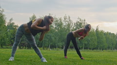 Young sexy sport women doing flexible exercising for body in the park Stock Footage
