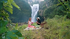 Two young women having picnic on grass in front of Tegenungan Waterfall, Ubud Stock Footage