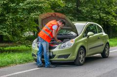 Young driver trying to repair a car, looking inside open bonnet - stock photo