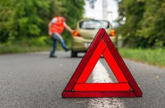 Angry driver kicking the tires on broken car and red warning trangle Stock Photos
