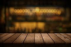 Wooden table with a view of blurred beverages bar backdrop Stock Photos